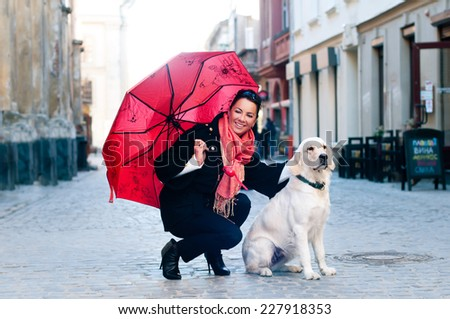 Pretty woman sits in old city with dog and looking at camera - stock photo