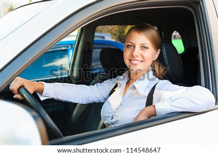 pretty woman sitting in the car and smiling - stock photo
