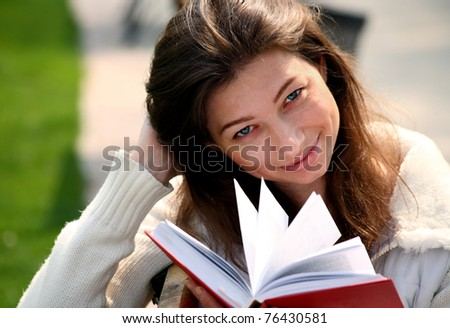 Pretty woman sitting on bench in park reading book smiling and looking into the camera - stock photo