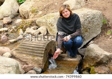 Pretty woman sitting on rocks near the stream - stock photo