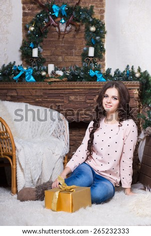 Pretty woman sitting on the white carpet with a golden gift box - stock photo