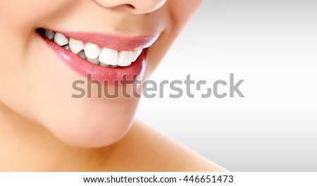 Pretty woman smiling against a grey background with copyspace - stock photo