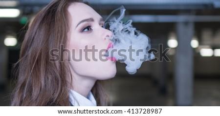 pretty woman smoking e-cigarette , shisha in the carpark - stock photo