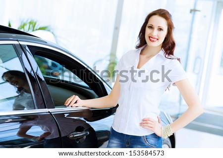 Pretty woman standing near car at car center. Choosing a car - stock photo