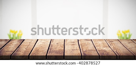 Pretty woman surprising her boyfriend with gift against wooden table - stock photo