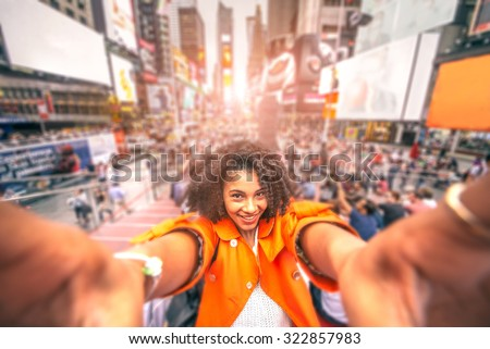 Pretty woman taking a selfie at Times Square, New York - Afroamerican girl taking a memorable self portrait with smartphone while traveling in a crowded city - stock photo