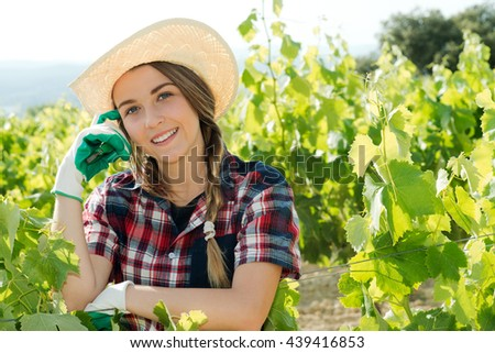 pretty woman taking care of plants looking at camera - stock photo