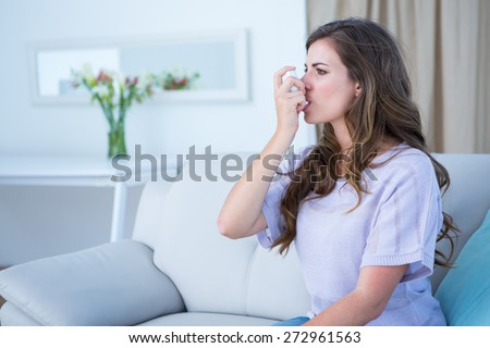 Pretty woman taking her inhaler at home at the living room - stock photo