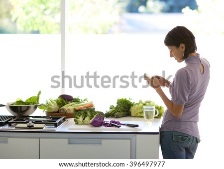 pretty woman talks on a mobile phone in the kitchen while preparing dinner  - stock photo