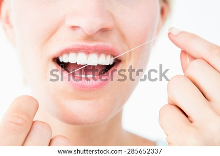 Pretty woman using dental floss on white background - stock photo