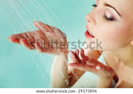 Pretty woman using fresh water in the bath room - stock photo