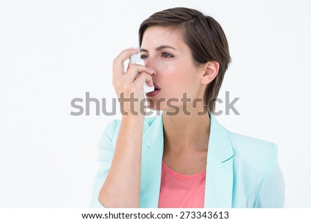 Pretty woman using her inhaler on white background - stock photo