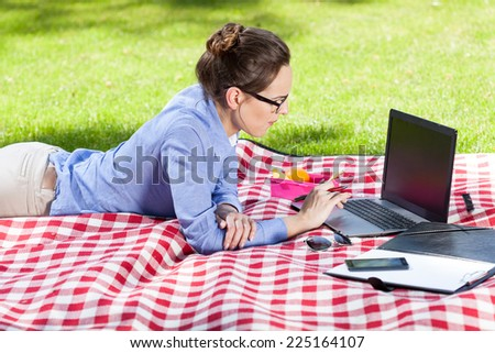 Pretty woman using her laptop lying on a blanket in the park on a sunny day - stock photo