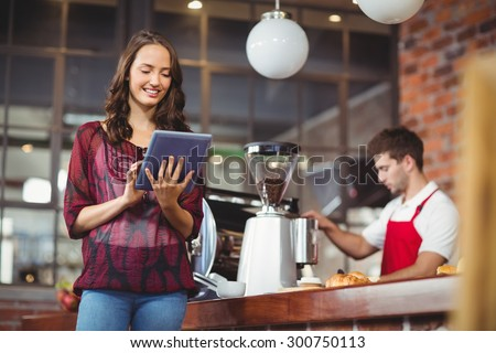 Pretty woman using her tablet at the coffee shop - stock photo