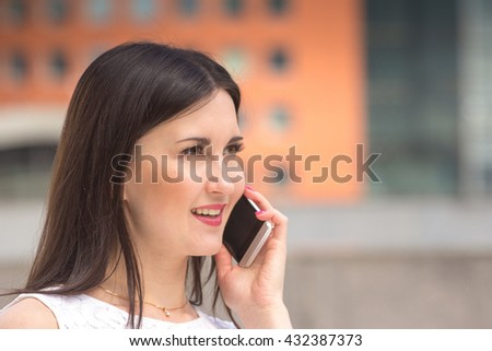 Pretty woman using mobile phone on urban background - stock photo