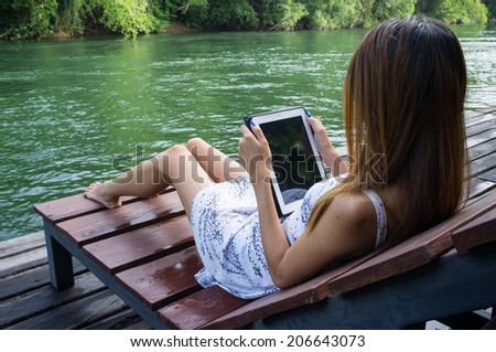 Pretty Woman using tablet PC sitting by the river kwai Kanchanaburi in Thailand  - stock photo