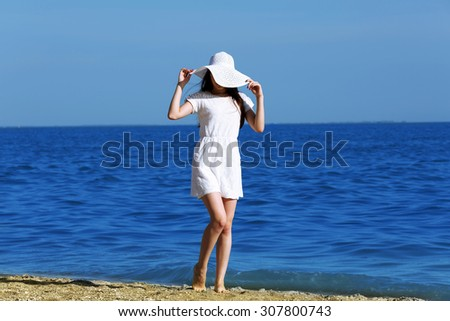 Pretty woman walking on beach - stock photo