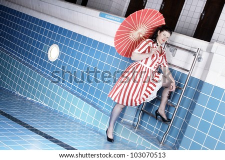 Pretty woman wearing a summer dress posing in an empty swimming pool - stock photo