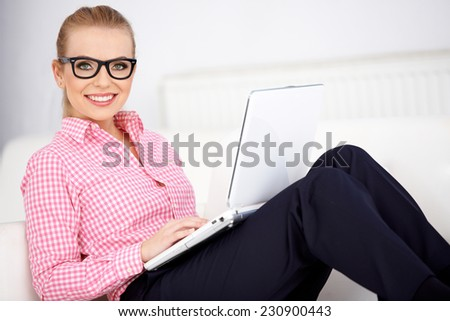 Pretty woman wearing glasses relaxing at home sitting on a comfortable sofa with her laptop balanced on her knees smiling at the camera - stock photo