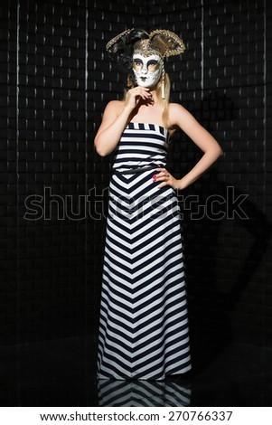 Pretty woman wearing long dress and mask posing near a black wall - stock photo