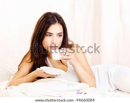 Pretty woman white dressed dink coffee in bed - stock photo