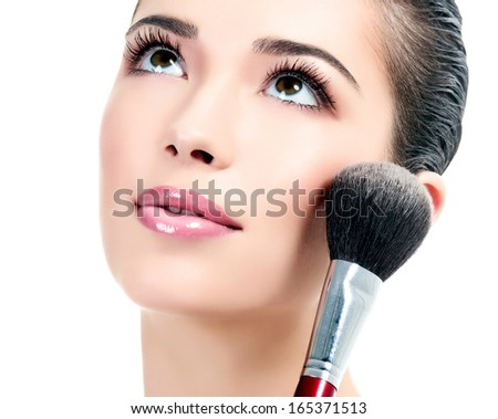 Pretty woman with a cosmetic brush, white background  - stock photo