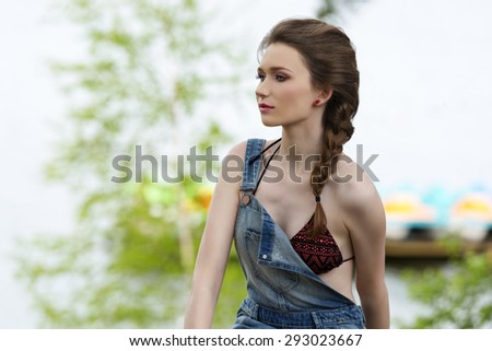 pretty woman with bikini and denim overall posing in outdoor summer portrait in the green nature with sea water on background  - stock photo