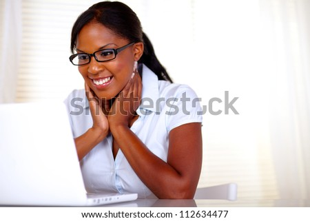 Pretty woman with black glasses working on laptop at office - copyspace - stock photo