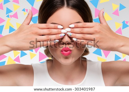 pretty woman with colorful gel nails hiding her eyes with fingers  - stock photo