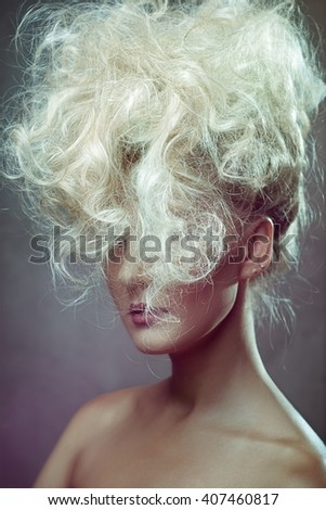 Pretty woman with curly hair on gray background - stock photo