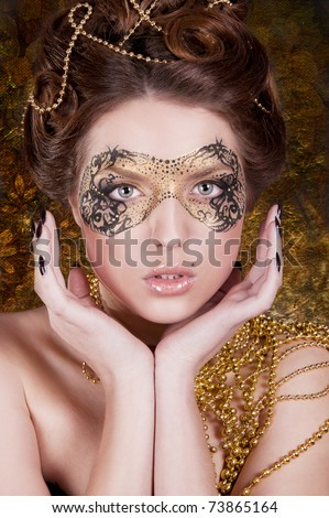 pretty woman with gold mask on gold background - stock photo