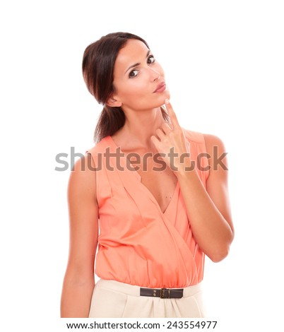 Pretty woman with hand on chin wondering while looking at you in white background - stock photo