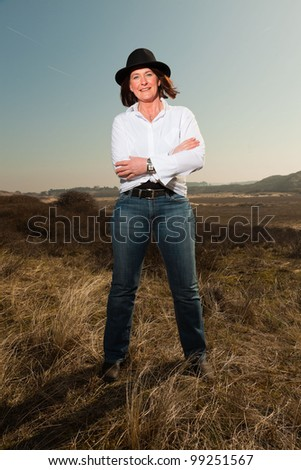 Pretty woman with hat middle aged enjoying outdoors. Clear sunny spring day with blue sky. - stock photo