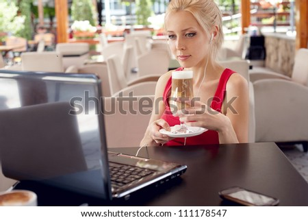 Pretty woman with laptop in cafe - stock photo