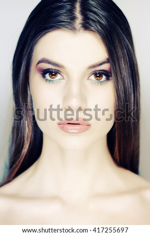 Pretty woman with long straight brown hair looking at camera. Beauty Woman Face closeup. Beauty Luxury Makeup and sexy nude color Lips.  - stock photo