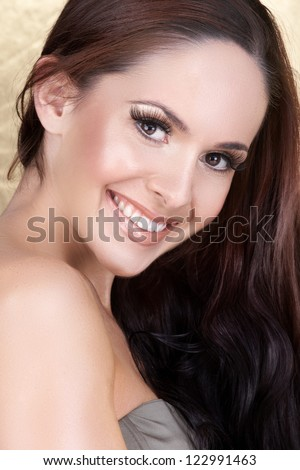 pretty woman with long straight brown hair with a happy smile on studio background - stock photo