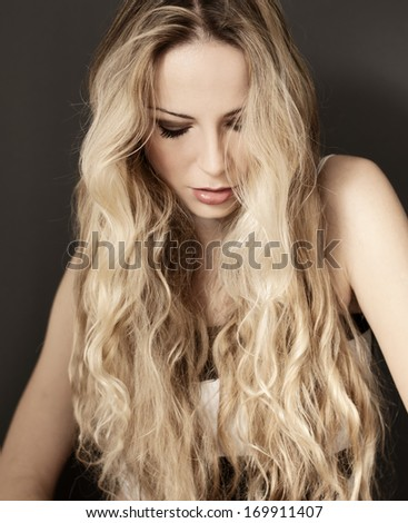 Pretty woman with long wavy blond hair  - stock photo