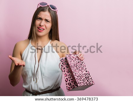 Pretty woman with pink glasses and shopping bag - stock photo