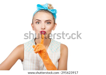 Pretty woman with rubber gloves is raising her finger to her mouth secretly. She wants somebody to be quiet. Isolated on background and copy space in right side - stock photo