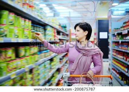 pretty woman with shopping cart choosing at goods in supermarket - stock photo