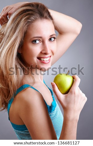 Pretty woman with smile holding green apple - stock photo