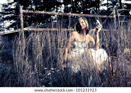 Pretty Woman with Vintage Camera in tall weeds and rusted fence. Photo in desaturated style. - stock photo