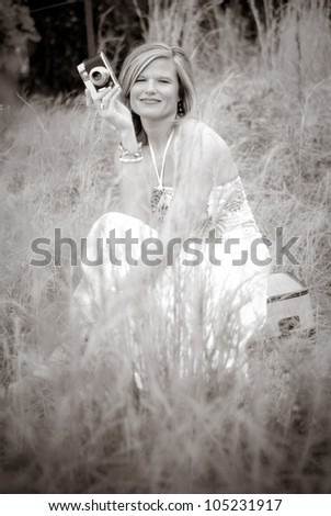 Pretty Woman with Vintage Camera sitting on suitcase in tall weeds. Photo in black and white. - stock photo