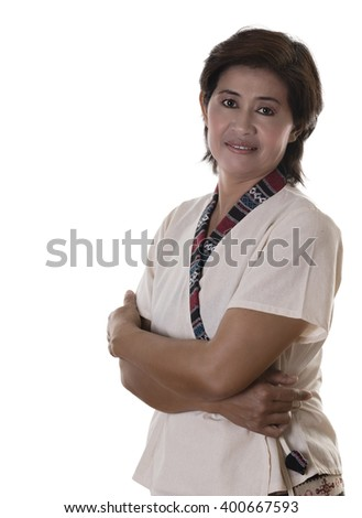 Pretty woman with white blouse and dark hair grins uncertainly while pressing crossed arms against her middle - stock photo