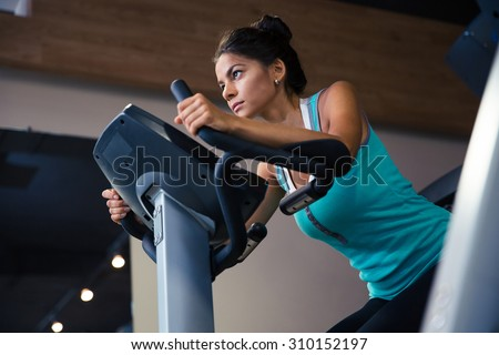 Pretty woman workout on exercises machine in fitness gym - stock photo