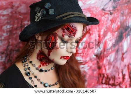 Pretty woman wound glass splinters in the skin, standing near bloody wall. Perfect idea for advertisement, banner, Halloween party card. Cosplay idea beauty monster, red sexy blood lips. Young face - stock photo
