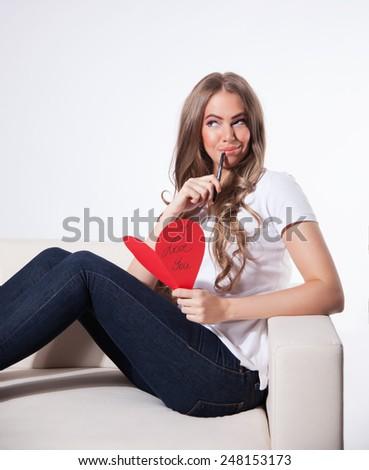 Pretty woman writing a love card - stock photo