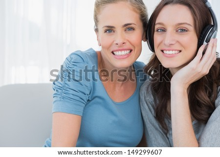Pretty women posing while listening to music sitting on the sofa - stock photo