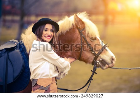 Pretty women with horse at field  - stock photo