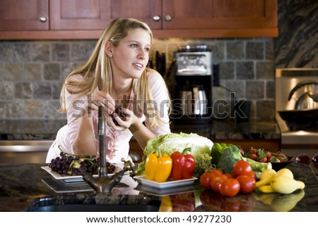 Pretty 17 year old teenage girl leaning on kitchen counter thinking - stock photo
